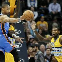 Photo - Oklahoma City Thunder's Russell Westbrook, left, make a pass with Denver Nuggets' Kenneth Faried, right, covering during the first quarter of an NBA basketball game Tuesday, Dec. 17, 2013, in Denver. (AP Photo/Barry Gutierrez)