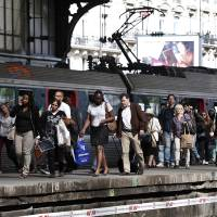 Photo - Commuters walk on a platform at the Gare St Lazare station in Paris, Wednesday,  June 11, 2014, as French rail workers strike to protest against plans to open the railways to competition. French commuters faced crowded trains Wednesday morning as a strike sharply reduced capacity, and a protest by taxi drivers in at least three European countries threatened to spread the misery. (AP Photo/Thibault Camus)