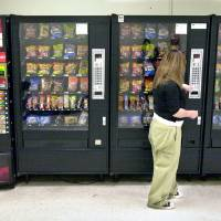 Photo - FILE - In this May 3, 2006 file photo, a student purchases a brown sugar Pop-Tart from a vending machine in the hallway outside the school cafeteria, in Wichita, Kan. High-calorie sports drinks and candy bars will be removed from school vending machines and cafeteria lines as soon as next year, replaced with diet drinks, granola bars and other healthier items the Agriculture Department said Thursday June 27, 2013.(AP Photo/The Wichita Eagle, Mike Hutmacher, File)