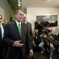 Photo - Speaker of the House John Boehner, R-Ohio, walks with House Ways and Means Committee Chairman Dave Camp, R-Mich., following a closed-door GOP meeting as the