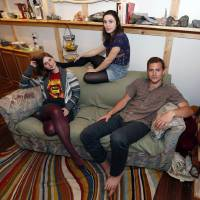 Photo - Lara Russo, left, Cally Guasti, center, and Reese Werkhoven sit on a couch in their apartment in New Paltz, N.Y. on Thursday, May 15, 2014. The roommates had purchased it at a Salvation Army store and found $40,800 stashed inside. After finding a deposit slip, they returned the money to the 91-year-old upstate New York widow who had hidden it there. (AP Photo/Mike Groll)