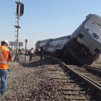 Photo -   Emergency personnel respond to the scene of a train derailment in Hanford, Calif., Monday, Oct. 1, 2012. Two cars and the locomotive of the train car derailed after colliding with a big rig truck in California's Central Valley, authorities said. At least 20 passengers suffered minor to moderate injuries, authorities said. The crash occurred when the driver of the big rig carrying cotton trash failed to yield and hit the train, authorities said. The impact pushed the two passenger cars and the locomotive off the tracks south of Hanford, a farming town. (AP Photo/Gosia Woznicacka)