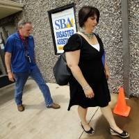 Photo - Heather Thompson,right, and FEMA IT specialist Kirk Thomas walk out of the disaster recovery center at Capitol Hill Baptist Church on Wednesday, July 17, 2013, in Oklahoma City, Okla.  Photo by Steve Sisney, The Oklahoman