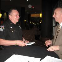Photo - Oklahoma County Sheriff John Whetsel shares a laugh Wednesday with keynote speaker Steve Scheibner after the 29th annual Metro Prayer Breakfast at the Cox Convention Center in Oklahoma City.  Photo by Carla Hinton, The Oklahoman