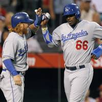 Photo - Los Angeles Dodgers' Justin Turner, left, congratulates Yasiel Puig after they scored on a single by Hanley Ramirez in the third inning of a baseball game against the Los Angeles Angels on Thursday, Aug. 7, 2014, in Anaheim, Calif. (AP Photo/Alex Gallardo)