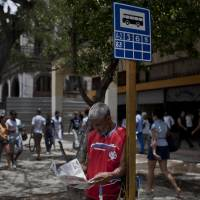 Photo - A man reads a copy of Cuba's state newspaper Granma while waiting for the bus in Havana, Cuba, Monday, May 19, 2014. Cuba's best-known blogger Yoani Sanchez and her husband Reinaldo Escobar say they will start publishing the country's first major independent general-interest newspaper in more than 50 years on Wednesday, in a move that will test both the government's openness to free expression and the dissident's ability to build a following inside her country. (AP Photo/Franklin Reyes)