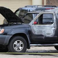 Photo -  Oklahoma City police and arson investigators are shown at the scene of a vehicle fire Wednesday in Oklahoma City. A body was found inside, but authorities say the death was not being investigated as foul play. Photo by Paul B. Southerland, The Oklahoman   PAUL B. SOUTHERLAND