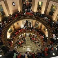 Photo - Protesters gather for a rally in the State Capitol rotunda in Lansing, Mich., Tuesday, Dec. 11, 2012. The crowd is protesting right-to-work legislation passed last week. Michigan could become the 24th state with a right-to-work law next week. Rules required a five-day wait before the House and Senate vote on each other's bills; lawmakers are scheduled to reconvene Tuesday and Gov. Snyder has pledged to sign the bills into law. (AP Photo/Paul Sancya)