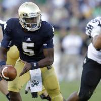 Photo -   FILE - In this Sept. 8, 2012, file photo, Notre Dame quarterback Everett Golson (5) looks to hand off the ball during the second half of an NCAA college football game against Purdue in South Bend, Ind. Golson didn't do much last time out to make anyone think he'll be the quarterback who will lead Notre Dame back to glory, but coach Kelly remains firmly behind him, saying he sees him developing every day in practice. (AP Photo/Michael Conroy, File)