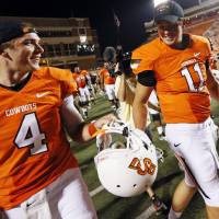 Photo - OSU quarterbacks J.W. Walsh, left, and Wes Lunt talk as they leave the field after a college football game between Oklahoma State University and Savannah State University at Boone Pickens Stadium in Stillwater, Okla., Saturday, Sept. 1, 2012. OSU won, 84-0. Photo by Nate Billings, The Oklahoman