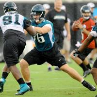 Photo - Jacksonville Jaguars first round draft pick Luke Joeckel, center, blocks Abry Jones during NFL football rookie minicamp Friday, May 3, 2013,  at EverBank Field in Jacksonville, Fla.  (AP Photo/The Florida Times-Union, Bob Self)