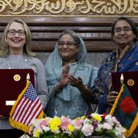 Photo -   Bangladesh prime minister Sheikh Hasina, center, applauds as U.S. Secretary of State Hillary Rodham Clinton, left, and Bangladesh Foreign Minster Dipu Moni pose for photographs after signing an agreement in Dhaka, Bangladesh, Saturday, May 5, 2012. Clinton is in Bangladesh to press tolerance, democracy and development in one of the world's most impoverished nations that is now in the throes of political turmoil. (AP Photo/Pavel Rahman)