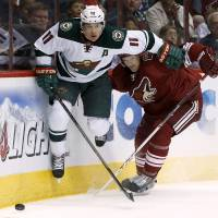 Photo - Minnesota Wild's Zach Parise (11) and Phoenix Coyotes' Zbynek Michalek, of the Czech Republic, collide behind the goal during the first period of an NHL hockey game, Saturday, March 29, 2014, in Glendale, Ariz. (AP Photo/Ross D. Franklin)