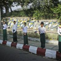 Photo -   Young boys and girls line the streets waving flags along the motorcade route in anticipation of the arrival of U.S. President Barack Obama, in Yangon, Myanmar, Monday, Nov. 19, 2012. (AP Photo/Pablo Martinez Monsivais)