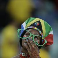Photo - A South Africa fan reacts as her team is knocked out of the African Cup of Nations after losing to Mali on penalties in their quarterfinal soccer match, at Moses Mabhida Stadium in Durban, South Africa, Saturday, Feb. 2, 2013. (AP Photo/Rebecca Blackwell)