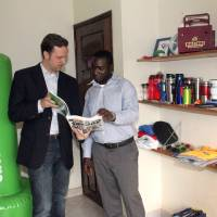 Photo -  Tyler and his employee, Francis, look through Inflate Africa's catalog of corporate gifts, with some of their products on display. Photo provided by Dani Walker Kreutter   Dani Walker Kreutter