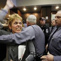 Photo - Pro-choice advocate Margaret Doyle from Richmond, Va., is removed by Capitol Police from the General Assembly Building in Richmond after HB1, the bill that states human life begins at conception, passed the Senate Education and Health committee on Thursday, Feb. 23, 2012. Eight Republicans voted for the measure, and the committee's seven Democrats opposed it after an hour-long hearing on the bill that is similar to one in Missouri. The vote now sends the bill to the full Senate where Democrats and Republicans hold 20 seats apiece. (AP Photo/Richmond Times-Dispatch, Bob Brown)