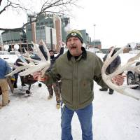 Photo - A Green Bay Packers fan shows off antlers as they tailgate before an NFL wild-card playoff football game between the Green Bay Packers and the San Francisco 49ers, Sunday, Jan. 5, 2014, in Green Bay, Wis. (AP Photo/Jeffrey Phelps)