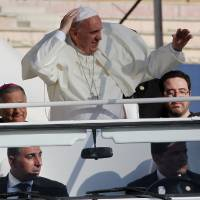 Photo - Pope Francis waves at audience members after his arrival at Amman's international stadium in Jordan, Saturday, May 24, 2014. Pope Francis called on Saturday for an