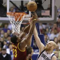 Photo - Dallas Mavericks center Chris Kaman (35) has his shot defended by Cleveland Cavaliers Tristan Thompson (13) and Luke Walton (4) during the first half of an NBA basketball game Friday, March 15, 2013, in Dallas. (AP Photo/LM Otero)