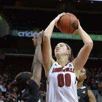 Photo - Louisville's Sara Hammond, right, shoots over the defense of Central Florida's Andrea Hunes during the first half of an NCAA college basketball game on Wednesday, Jan. 15, 2014, in Louisville, Ky. (AP Photo/Timothy D. Easley)
