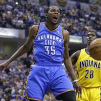 Photo - Oklahoma City Thunder forward Kevin Durant reacts after a dunk in front of Indiana Pacers center Ian Mahinmi in the first half of an NBA basketball game in Indianapolis, Sunday, April 13, 2014. (AP Photo/Michael Conroy)