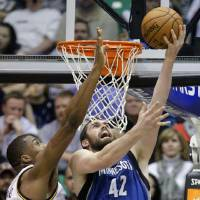 Photo - Minnesota Timberwolves power forward Kevin Love (42) lays the ball up as Utah Jazz power forward Derrick Favors (15) defends in the third quarter during an NBA basketball game on Wednesday, Jan. 2, 2013, in Salt Lake City.   (AP Photo/Rick Bowmer)