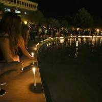 Photo - Students and supporters place candles at the edge of a wall surrounding a pond as they take part in a candle light vigil at the University of Central Florida, Wednesday, Sept. 3, 2014, in Orlando, Fla., to honor Steven Sotloff, the second American journalist to be beheaded by the Islamic State group in two weeks. Sotloff attended University of Central Florida between 2002 and 2004. (AP Photo/John Raoux)