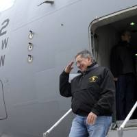 Photo - U.S. Defense Secretary Leon Panetta salutes as he walks off of his plane after arriving at Kandahar Airfield in Kandahar, Afghanistan, Thursday, Dec. 13, 2012. (AP Photo/Susan Walsh, Pool)