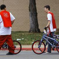 Photo - Volunteers walk three bicycles to a waiting vehicle during The  Salvation Army and Feed The Children distribution event.