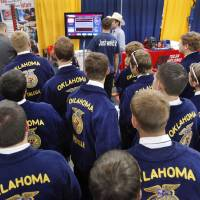 Photo - A large group of boys gather around the booth sponsored by the Tulsa Welding School to watch some of their fellow FFA members do a welding demonstration at the trade show during the annual state convention of FFA members at the Cox Convention Center in Oklahoma City,  on Tuesday, May 1, 2012.    Photo by Jim Beckel, The Oklahoman