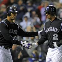 Photo -   Colorado Rockies' Carlos Gonzalez (5) and Troy Tulowitzki (2) celebrate being driven in on a Todd Helton two-RBI single against the Arizona Diamondbacks during the fourth inning of a baseball game on Friday, April 13, 2012, in Denver. (AP Photo/Jack Dempsey)