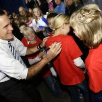 Photo -   Republican presidential candidate and former Massachusetts Gov. Mitt Romney signs shirts for children as he campaigns at the Iowa Events Center, in Des Moines, Sunday, Nov. 4, 2012. (AP Photo/Charles Dharapak)
