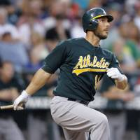 Photo -   Oakland Athletics' George Kottaras watches his two-run home run off Seattle Mariners' Hisashi Iwakuma during the fourth inning of a baseball game in Seattle on Saturday, Sept. 8, 2012. (AP Photo/John Froschauer)