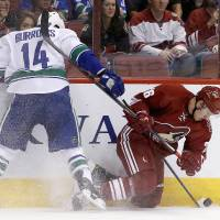 Photo - Vancouver Canucks' Alex Burrows (14) sends Phoenix Coyotes' Michael Stone, right, to the ice, but Burrows is called for a penalty, during the first period of an NHL hockey game on Tuesday, March 4, 2014, in Glendale, Ariz. (AP Photo/Ross D. Franklin)