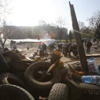 Photo - People gather in front of a barricade across a street in Slovyansk, eastern Ukraine, Wednesday, April 16, 2014. The city of Slovyansk has come under the increasing control of the pro-Russian gunmen who seized it last weekend. (AP Photo/Sergei Grits)