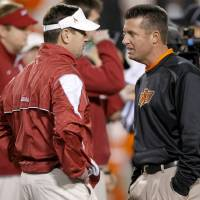 Photo - Oklahoma coach Bob Stoops, left, and Oklahoma State coach Mike Gundy talk before the Bedlam college football game between the University of Oklahoma Sooners (OU) and the Oklahoma State University Cowboys (OSU) at Boone Pickens Stadium in Stillwater, Okla., Saturday, Nov. 27, 2010. Photo by Bryan Terry, The Oklahoman ORG XMIT: KOD