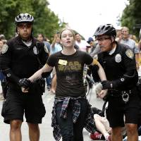 Photo - FILE -- In this Aug. 1, 2013 file photo, Seattle police officers take Caroline Durocher, center, into custody after Durocher sat in a downtown intersection during a protest by fast food workers and supporters in Seattle. Durocher works at a Subway sandwich shop. Washington already has the nation's highest state minimum wage at $9.19 an hour. Now, there's a push in Seattle, at least, to make it $15. That would mean fast food workers, retail clerks, baristas and other minimum wage workers would get what protesters demanded when they shut down a handful of city restaurants in May and others demonstrated nationwide in July. (AP Photo/Elaine Thompson, File)