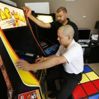 Photo - Jose Rodriguez, left, and Mark Temple demonstrate 1980s video games. Photo By Steve Gooch, The Oklahoman  Steve Gooch