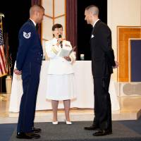"Photo -   ADVANCE FOR USE THURSDAY, JULY 5, 2012 AND THEREAFTER - In this Saturday, June 23, 2012 photo provided by Jeff Sheng, Navy Chaplain Kay Reeb of the Evangelical Lutheran Church of America officiates the civil union ceremony of Air Force Tech. Sgt. Erwynn Umali, right, and his partner Will Behrens at Joint Base McGuire-Dix-Lakehurst, the military base in Wrightstown, N.J. where Umali is stationed. Prior to repeal of the the ""don't ask, don't tell"" policy nine months ago, various conservative groups and individuals - including many conservative retired chaplains - warned that repeal would trigger an exodus of chaplains whose faiths consider homosexual activity to be sinful. In fact, there's been no significant exodus Moreover, chaplains or their civilian coordinators from a range of conservative faiths told The Associated Press they knew of virtually no serious problems thus far of repeal-related infringement of chaplains' religious freedom and rights of conscience. (AP Photo/Jeff Sheng)"