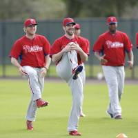 Photo - Philadelphia Phillies starting pitcher Cliff Lee, center, stretches with teammates during spring training baseball practice Thursday, Feb. 13, 2014, in Clearwater, Fla. (AP Photo/Charlie Neibergall)