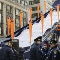 Photo - New York City police patrol next to a toboggan run in Super Bowl Boulevard, Tuesday, Jan. 28, 2014 in Times Square.  Thirteen blocks of midtown Manhattan have been converted into a temporary festival space leading up to the National Football League's championship game between the Seattle Seahawks and the Denver Broncos on  Sunday, Feb. 2, in East Rutherford, NJ. (AP Photo/Mark Lennihan)