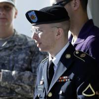 Photo - Army Pfc. Bradley Manning, front, is escorted out of a courthouse in Fort Meade, Md., Tuesday, June 4, 2013, after the second day of his court martial. Manning is charged with indirectly aiding the enemy by sending troves of classified material to WikiLeaks. He faces up to life in prison. (AP Photo/Patrick Semansky)