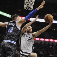 Photo - San Antonio Spurs guard Manu Ginobili, right, of Argentina, shoots against Orlando Magic center Nikola Vucevic during the first half of an NBA basketball game on Saturday, March 8, 2014, in San Antonio. (AP Photo/Darren Abate)