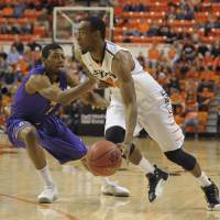 Photo - Oklahoma State guard, Markel Brown, right, drives past Tennessee Tech guard, Javon McKay, left, during the first half of an NCAA college basketball game,  Saturday, Dec. 22, 2012, in Stillwater, Okla. (AP Photo/Brody Schmidt)