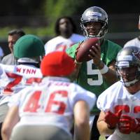 Photo -   Tampa Bay Buccaneers quarterback Josh Freeman (5) looks for a receiver as he runs through a play during NFL football practice, Thursday, June 14, 2012, in Tampa, Fla.(AP Photo/Brian Blanco)