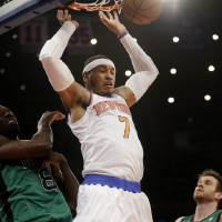 Photo - New York Knicks' Carmelo Anthony dunks over Boston Celtics' Jeff Green, left, and Shavlik Randolph during the first half of the NBA basketball game at Madison Square Garden, Sunday, March 31, 2013, in New York. (AP Photo/Seth Wenig)