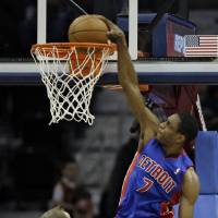 Photo - Detroit Pistons' Brandon Knight (7) dunks over Cleveland Cavaliers' Tyler Zeller (40) and Tristan Thompson (13) in the second quarter of an NBA basketball game on Wednesday, April 10, 2013, in Cleveland. (AP Photo/Mark Duncan)