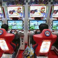 Photo - FILE - In this Feb. 15, 2013 file photo, visitors try out the Mario Kart Arcade GP DX racing game exhibited by Namco Bandai and Nintendo on the business day of the Japan Amusement Expo in Makuhari, near Tokyo. Nintendo Co. reported Wednesday, April 24, the Kyoto-based maker of Super Mario and Pokemon games returned to profit for the fiscal year ended March 31 as a lift from the weak yen offset sales struggles caused by software delays for its latest home console Wii U. (AP Photo/Koji Sasahara, File)