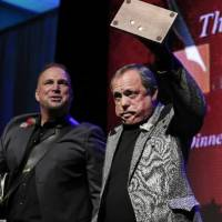 Photo -  Kim Williams acknowledges the audience as he is inducted into the Nashville Songwriters Hall of Fame on Sunday, Oct. 7, 2012, in Nashville, Tenn. Garth Brooks watches at left.